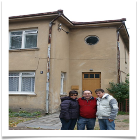 Eli and his wife and son infront of Meir Rutstein's house